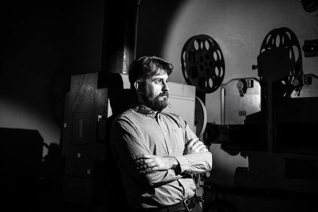 Homem parado perto de um projetor de cinema na sala projecionista