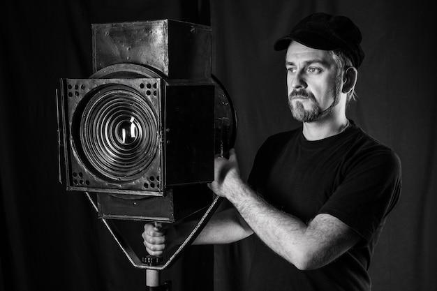 Homem parado perto de um projetor de filme