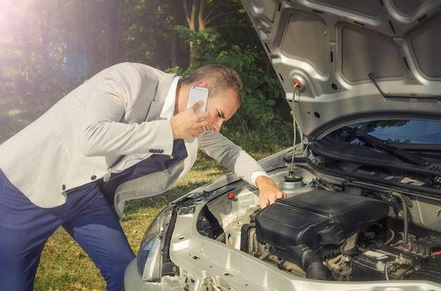 Homem parado perto do capô, fazendo uma ligação e tentando consertar o veículo.