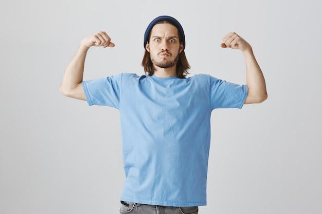 Homem parece tenso ao mostrar força, flexiona o bíceps sentindo-se fortalecido