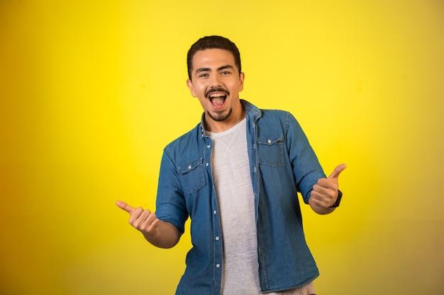Homem parecendo bem sucedido com polegares para cima e sorrindo.