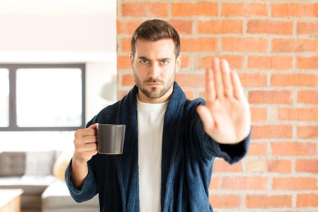 Homem parecendo sério, severo, descontente e irritado mostrando a palma da mão aberta fazendo gesto de pare