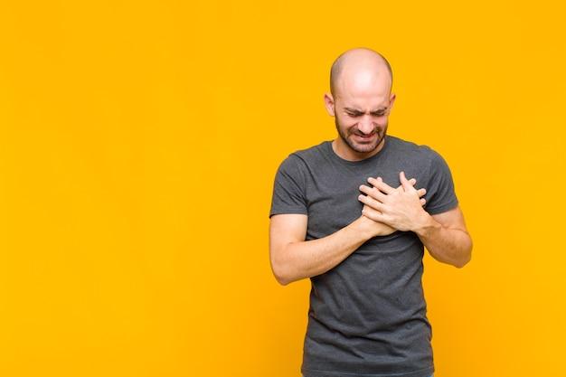Homem parecendo triste, magoado e com o coração partido, segurando as duas mãos perto do coração, chorando e se sentindo deprimido