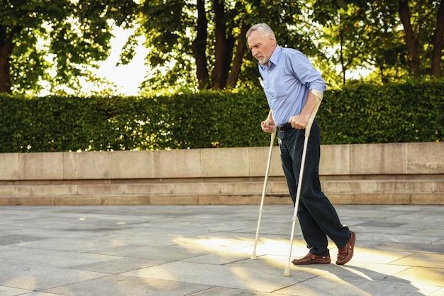 Homem passa no parque com muletas. homem em terapia.