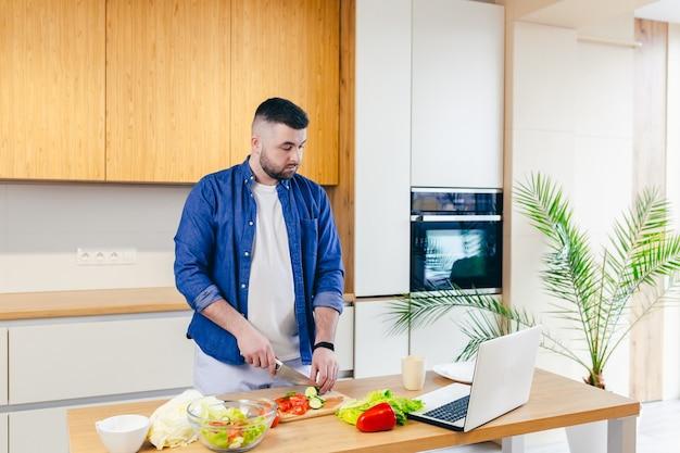 Homem passa o dia em casa prepara café da manhã com vegetais na cozinha homem com roupa de casa e barba usa laptop para aprender culinária online