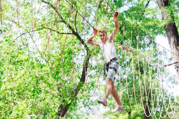 Homem passa seu tempo de lazer em um curso de cordas. homem envolvido no parque de corda.