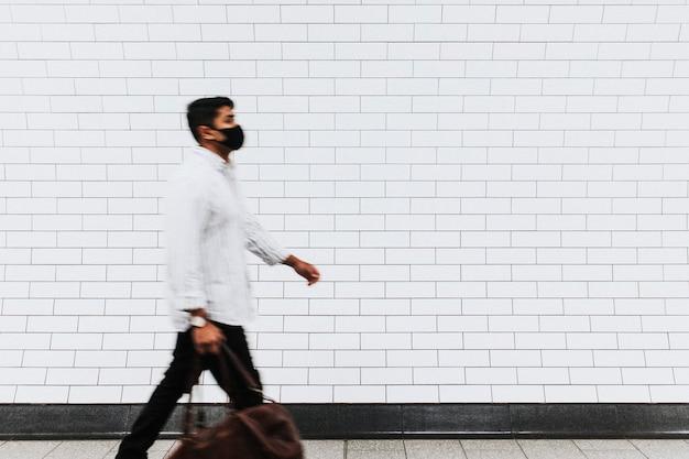 Homem passando por uma parede de tijolos brancos