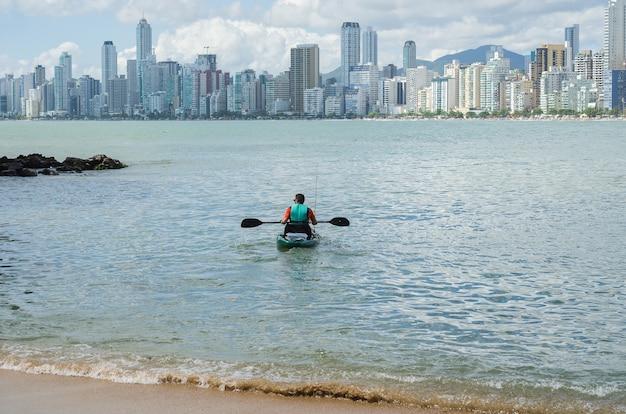 Homem passeando de caiaque em praia brasileira