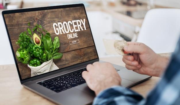 Homem pede comida pela internet usando um laptop