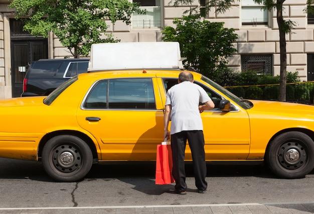 Homem pede informações um motorista de táxi em manhattan.