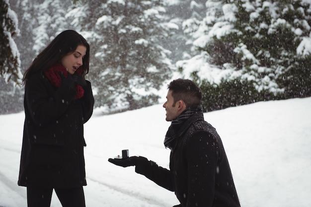 Homem pedindo mulher em casamento com anel na floresta durante o inverno