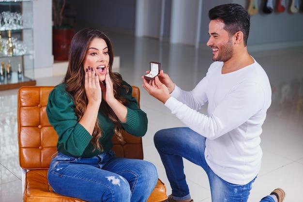 Homem pedindo para a namorada se casar com ele mostrando o anel para ela