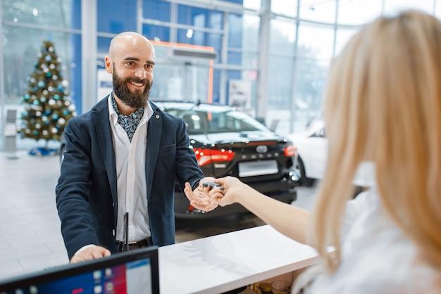 Homem pega a chave do carro novo na concessionária. cliente e vendedora em showroom de veículos, homem comprando transporte, concessionária de automóveis