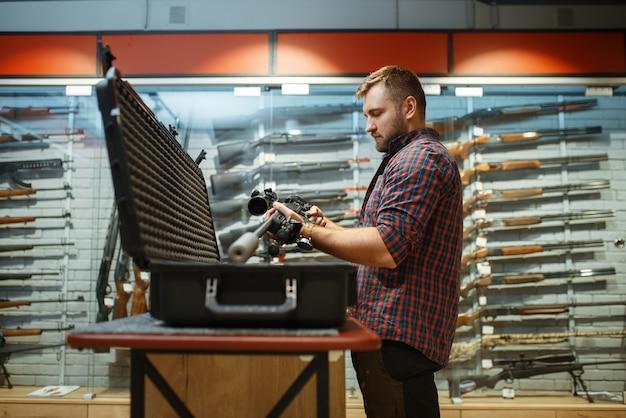 Homem pega rifle de atirador da caixa na loja de armas