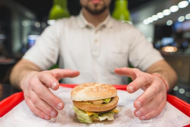 Homem pega um hambúrguer grande que está de pé na bandeja. as mãos são atraídas para o saboroso cheeseburger. concentre-se no hambúrguer.