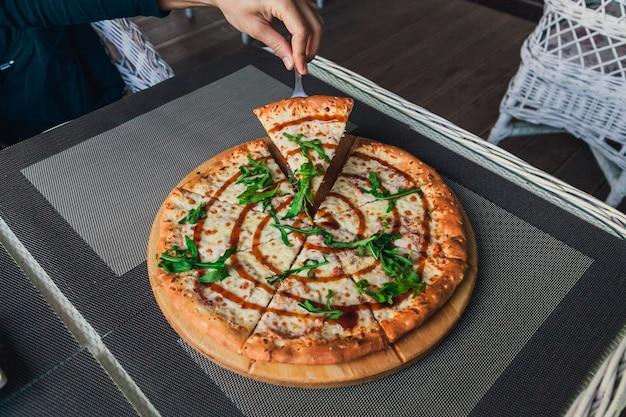 Homem pega uma fatia de pizza de um todo sobre um fundo cinza em um café de rua, vista superior.