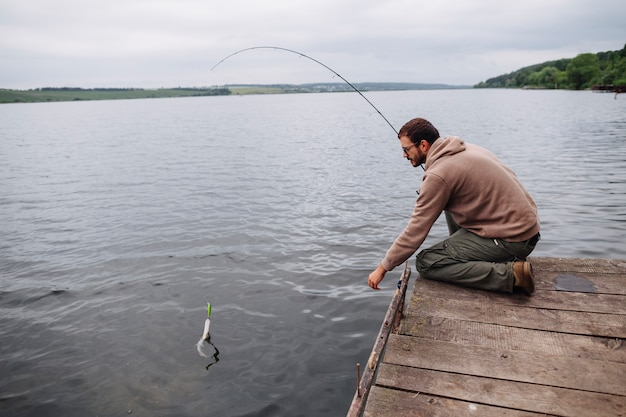 Homem, pegando peixe, com, cana de pesca, em, lago
