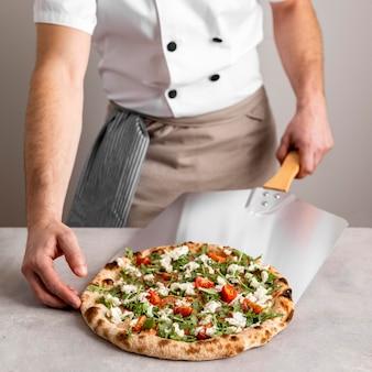 Homem pegando pizza com ferramenta para descascar