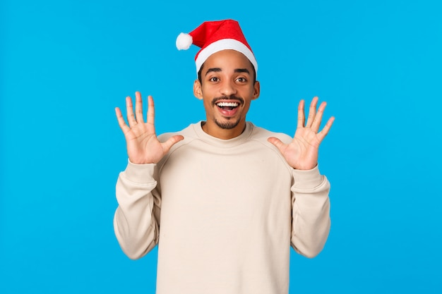 Homem pegando presentes no chapéu de papai noel. alegre jovem afro-americano pegar algo, levantando as mãos e esperando a captura, sorrindo com alegria, comemorar férias de inverno, parede azul