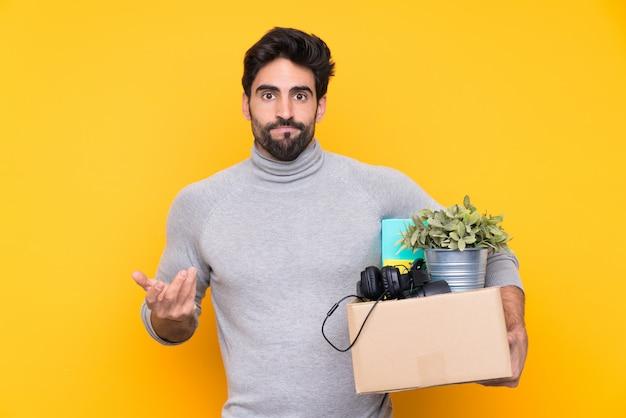 Homem pegando uma caixa cheia de coisas ao longo da parede isolada