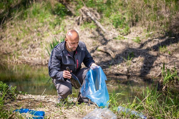 Homem pegando uma garrafa de plástico, coletando lixo no planeta de limpeza da floresta, ajudando na coleta de lixo, ambiente de caridade