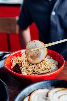 Homem pegar porco chashu fora da tigela por pauzinhos de shoyu chashu ramen por sua mão.