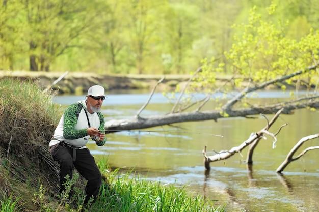 Homem peixe com fiação na margem do rio, isca de fundição. atividade de fim de semana ao ar livre. foto com profundidade de campo rasa tirada em grande abertura.