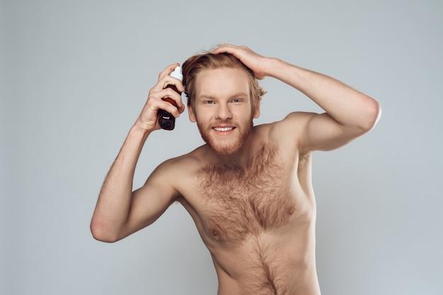 Homem peludo barbudo polvilha loção no cabelo em casa.