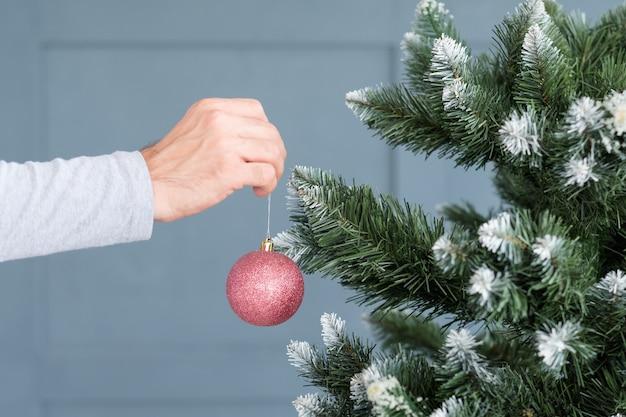 Homem pendurado bola brilhante de ouro rosa no pinheiro. conceito de ornamento festivo do feriado.