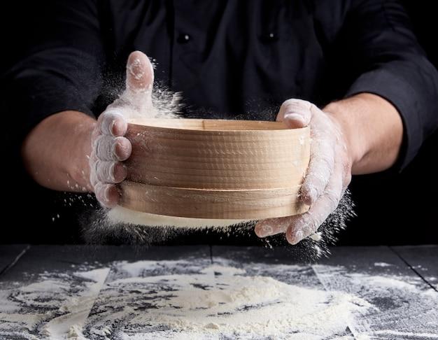 Homem peneira farinha de trigo branca através de uma peneira de madeira