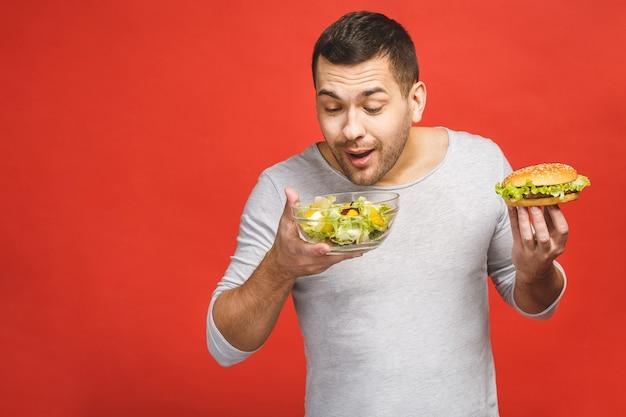 Homem pensando em escolher entre salada e hambúrguer, comida saudável e junk food.