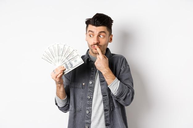 Homem pensando em fazer compras enquanto olha para as notas de dólar, segurando dinheiro e olhando pensativo, de pé sobre fundo branco.