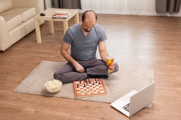 Homem pensando em seu próximo movimento em uma partida de xadrez com seus amigos durante uma videochamada em um momento de auto-isolamento.