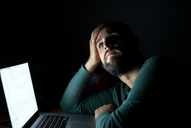 Homem pensando na frente do computador
