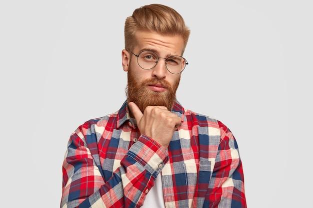 Homem pensativo com a barba por fazer segura o queixo, olha pensativo diretamente para a câmera, pensa em algo importante, vestido com uma elegante camisa xadrez