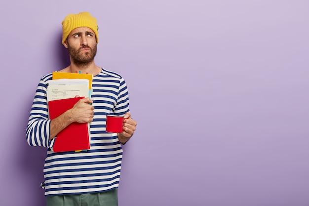 Homem pensativo com a barba por fazer segura uma xícara de café vermelha, papéis e um bloco de notas, estuda dentro de casa e usa uma roupa casual