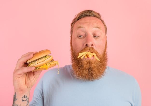 Homem pensativo com barba e tatuagens comendo um sandwitch com hambúrguer e batatas