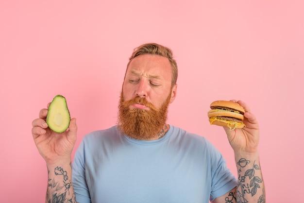 Homem pensativo com barba e tatuagens está indeciso se comer um abacate ou um hambúrguer