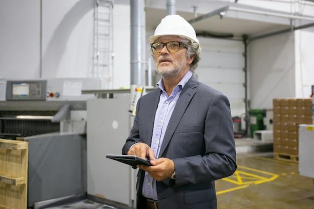 Homem pensativo com capacete protetor, segurando o tablet e desviando o olhar