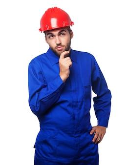 Homem pensativo com um macacão azul e um capacete vermelho
