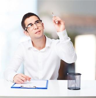 Homem pensativo com uma caneta no desenho da mão no ar