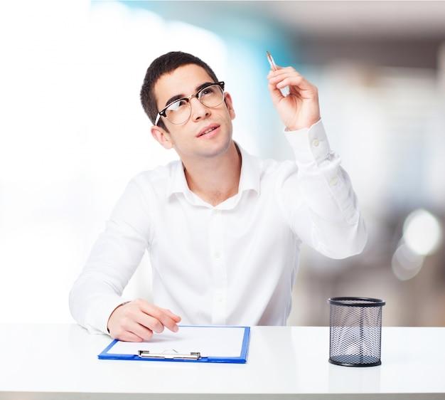 Homem pensativo com uma mesa de caneta esferográfica e verificação