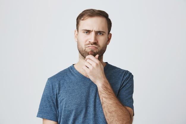 Homem pensativo de aparência séria que toma a decisão
