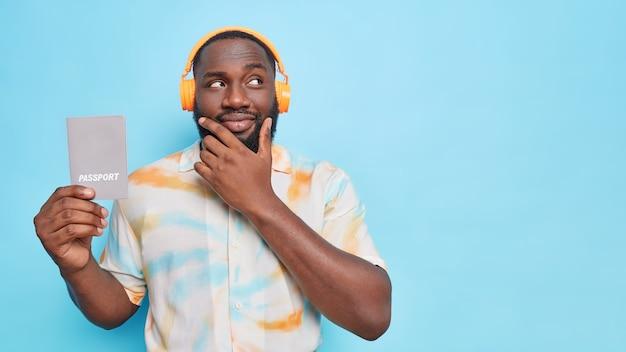 Homem pensativo de barba negra segura o queixo olhando para longe segura passaporte que contém informações básicas de identificação ouve música por meio de fones de ouvido sem fio isolados sobre a parede azul