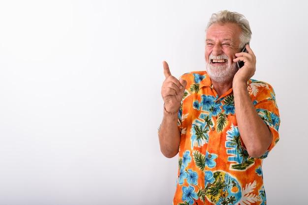 Homem pensativo e feliz turista barbudo sênior sorrindo e rindo enquanto fala no celular e aponta o dedo no branco