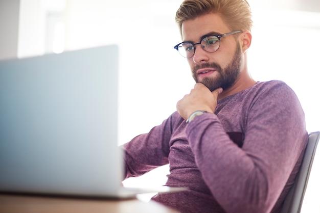 Homem pensativo e focado na frente do computador