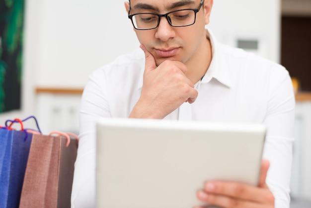 Homem pensativo, fazer compras e navegar no computador tablet