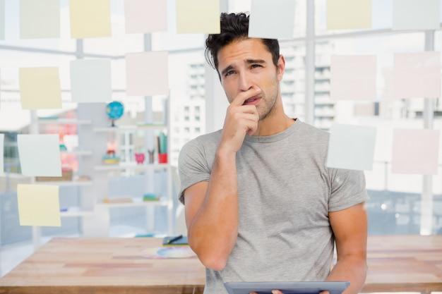 Homem pensativo olhando notas auto-adesivas na janela