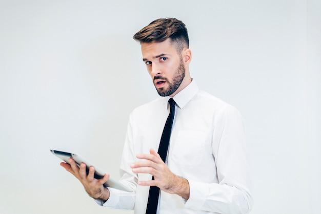 Homem pensativo olhando para um tablet