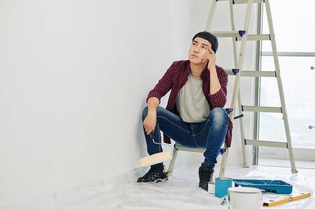 Homem pensativo olhando para uma parede pintada